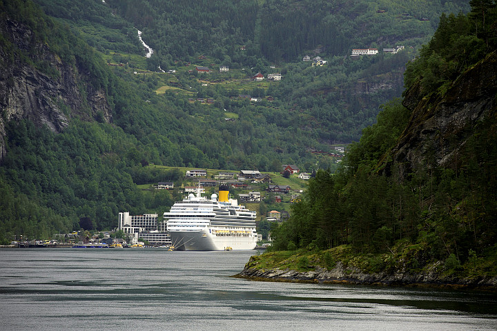 Large cruiseship in the Geiranger Fjord, surrounded by mountains