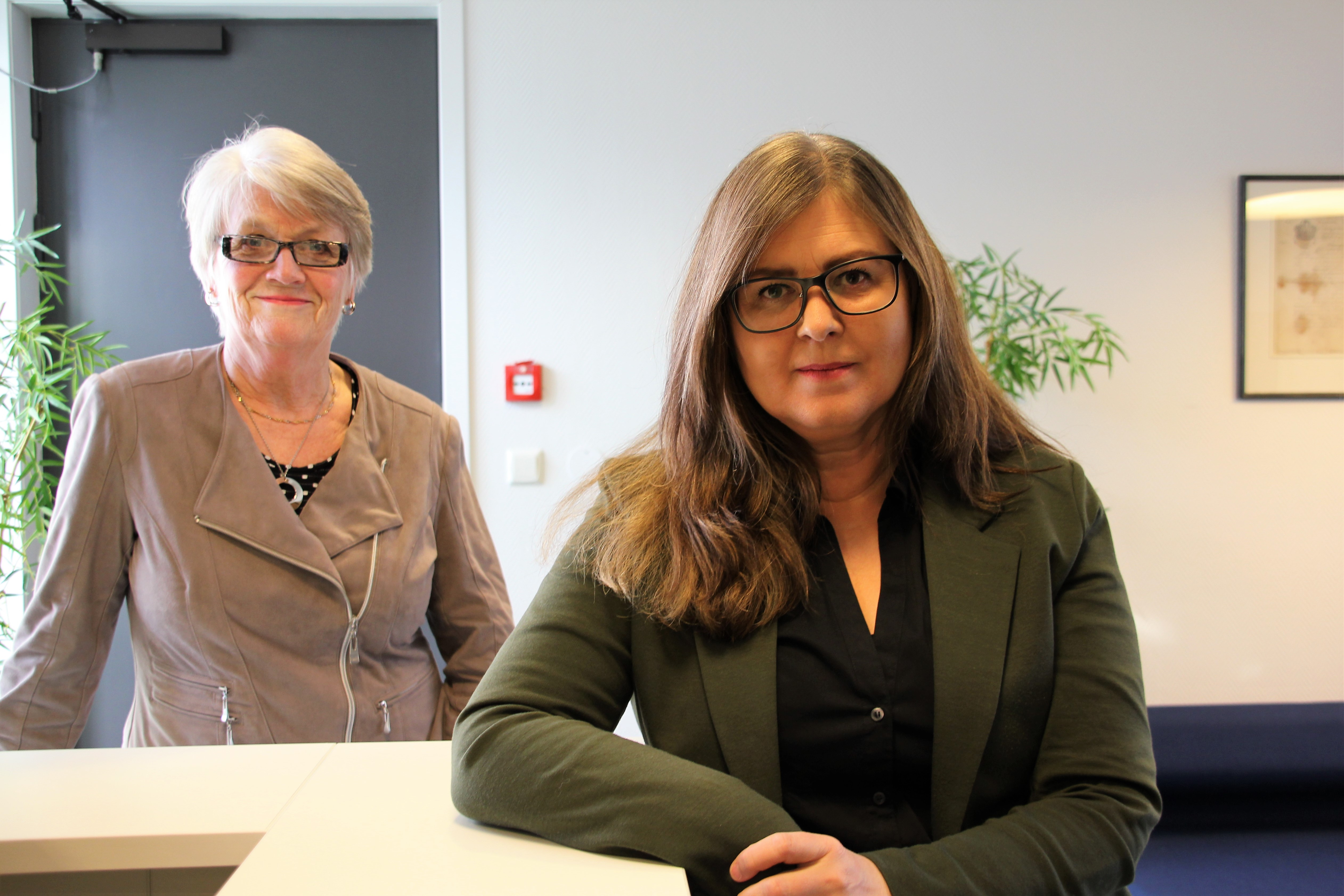 The picture shows to women, Anita Malmedal and Monika Borge, standing by a desk, smiling.