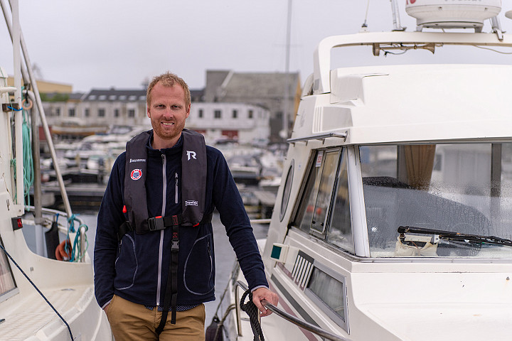 Petter Andre Søreng standing next to a yacht, wearing a safety jacket