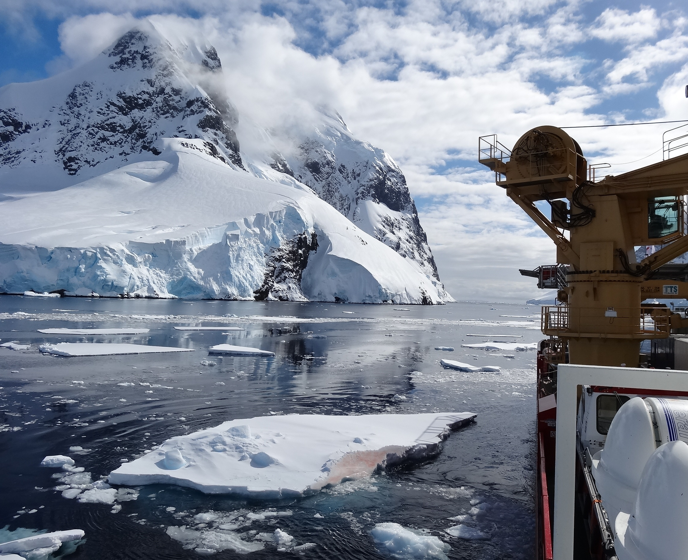 Picture of a ship at sea close to ice bergs.