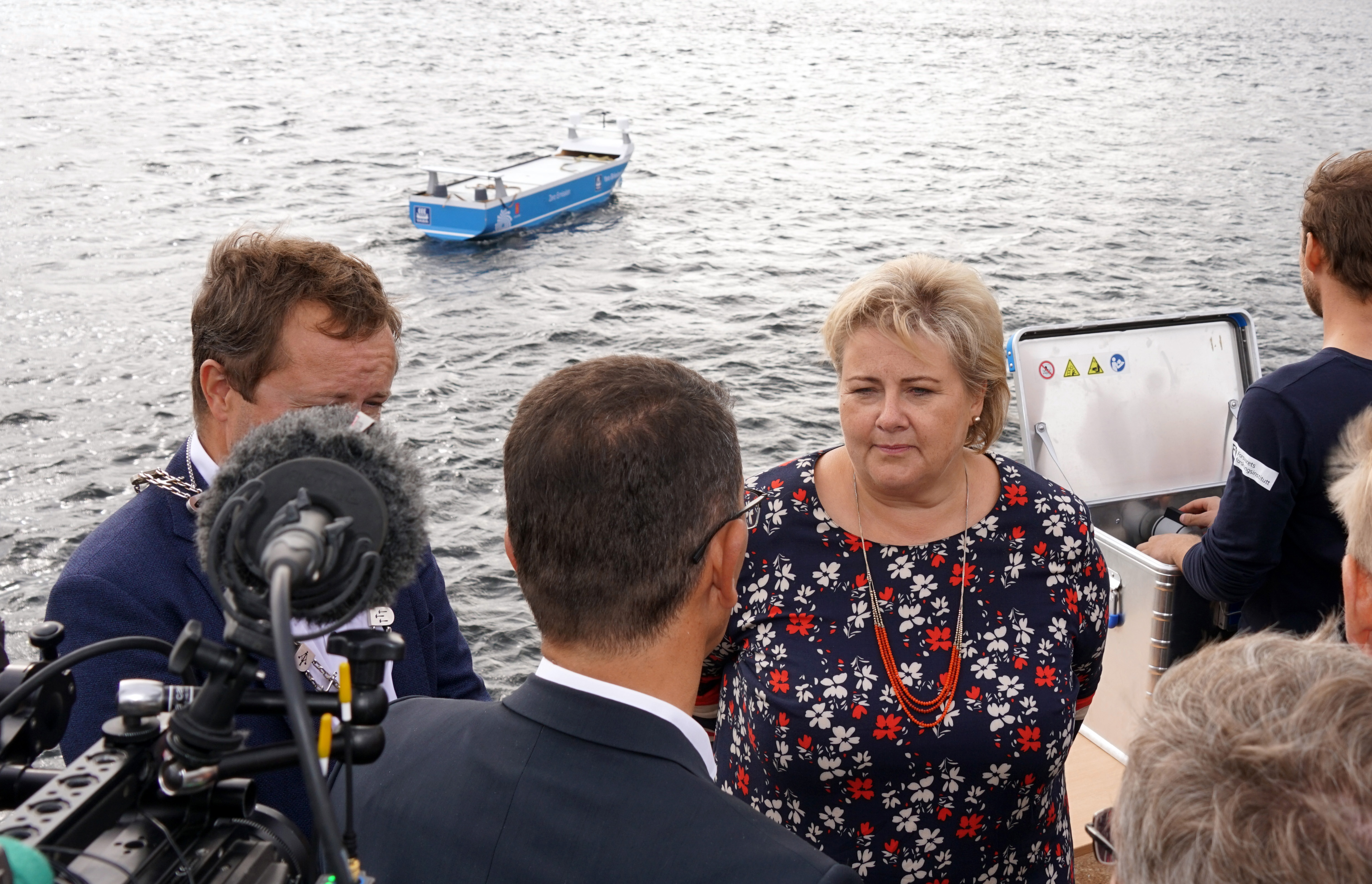 Norwegian prime minister Erna Solberg in front of a miniature version of Yara Birkeland, and several press offisers in front.