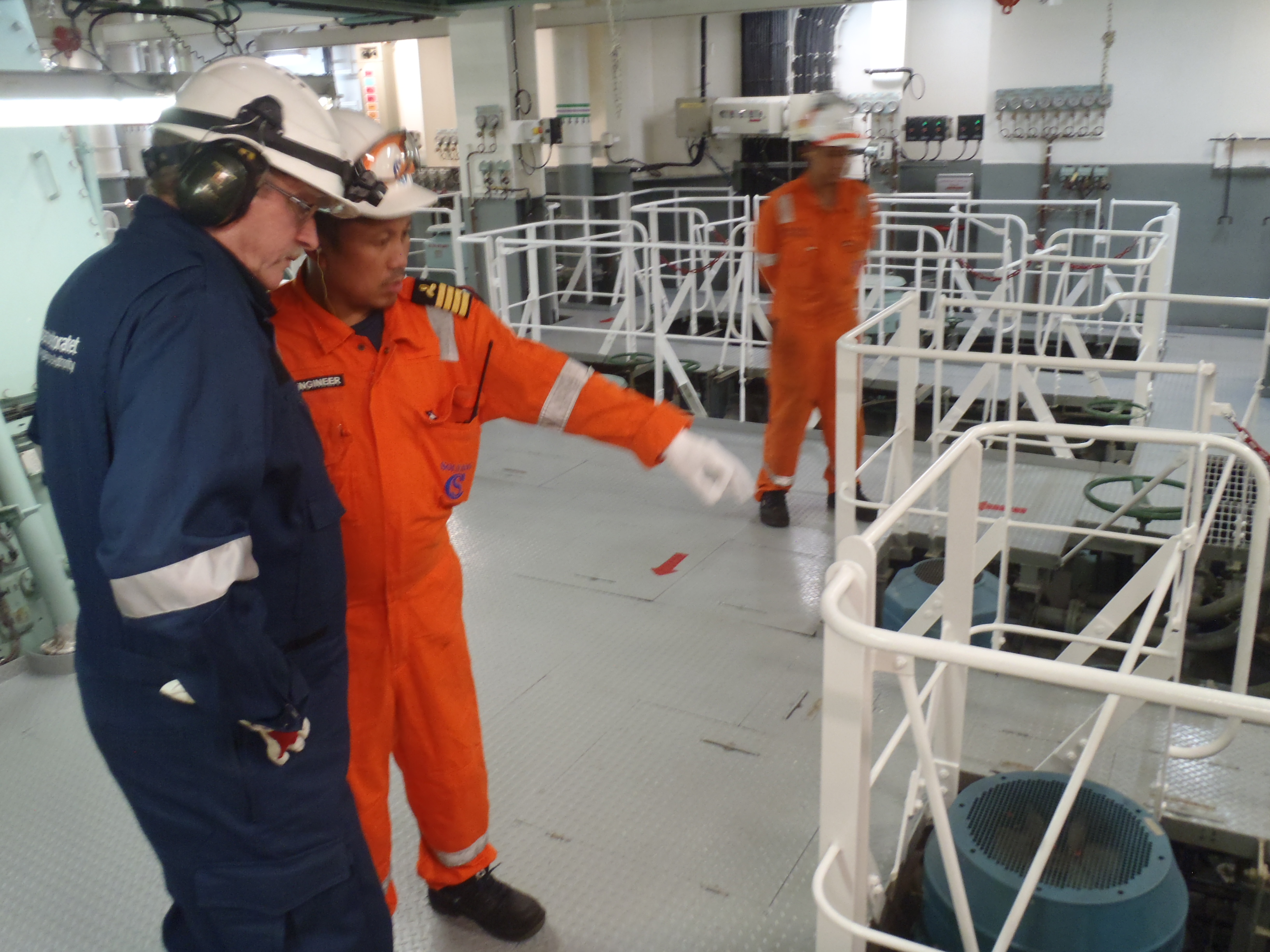 A uniformed surveyor (Kjell Jakobsen) is talking to the chief engineer on board a ship.