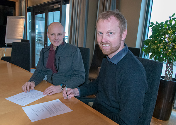 Petter Søreng and Bernt Nilsen signing a contract in an office environment.