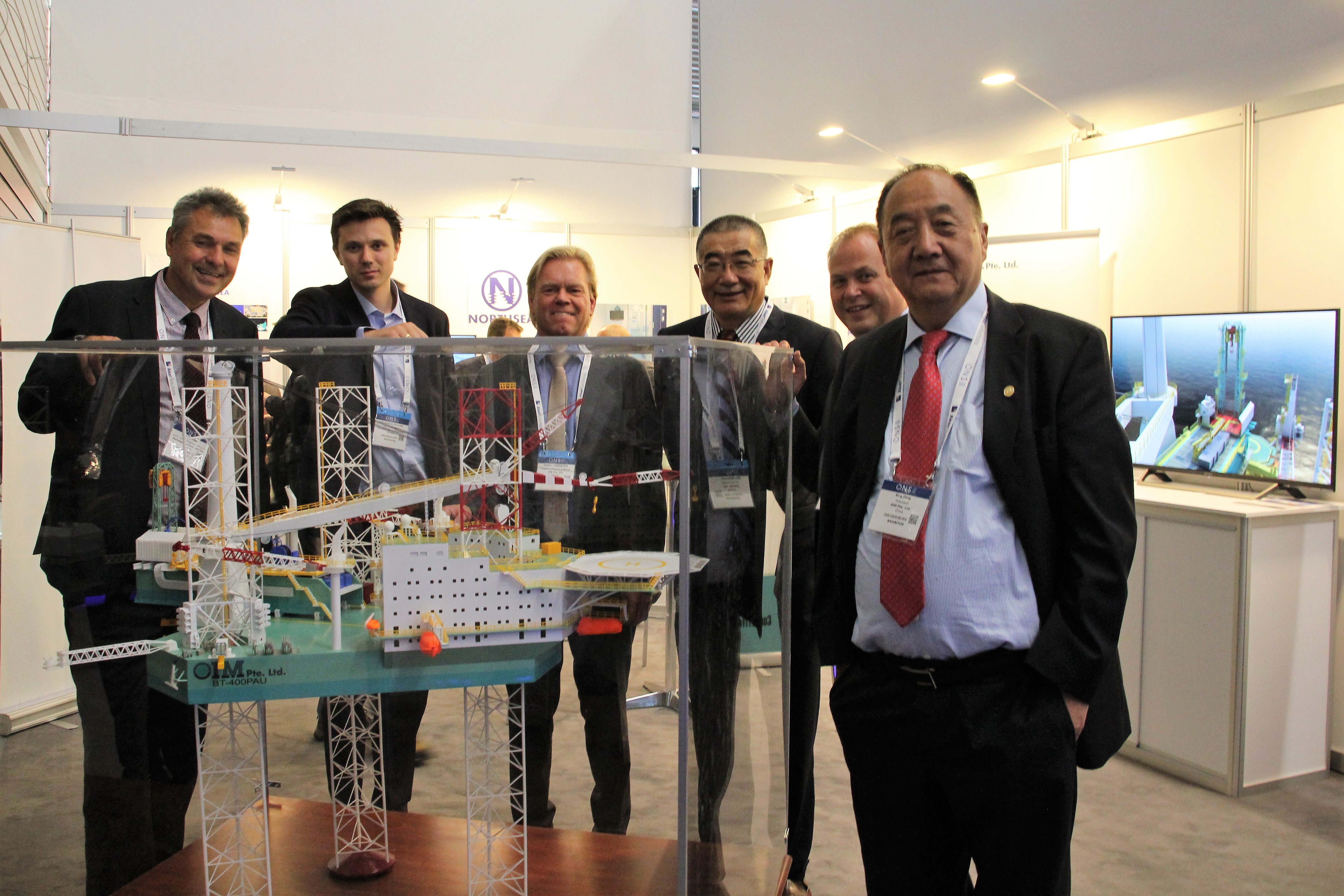Six men in suits aurroundig a model of aan offshore rig.