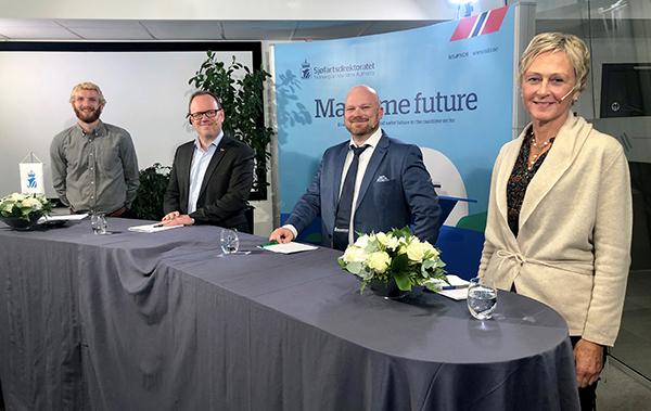 På bildet ser du tre menn og en kvinne klare til å delta i en paneldebatt.